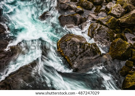 Turquoise water with moss stones in Iceland. Artistic picture