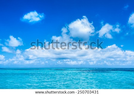 Turquoise waters and gentle waves of a Caribbean beach with deep blue sky. - stock photo