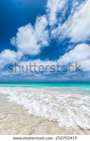 Turquoise waters and gentle waves of a white sand Caribbean beach with deep blue sky. - stock photo