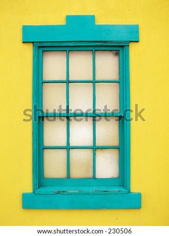 turquoise window, yellow wall - stock photo
