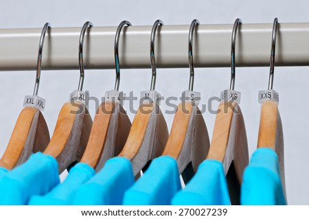 Turquoise women's t-shirts hang on wooden hangers with indexes of the XXS, XS, S, M, L, XL, XXL sizes on a light background. - stock photo