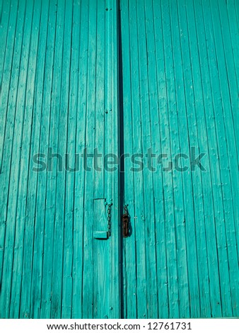 Turquoise wooden entrance door with chain