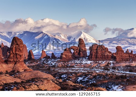 Turret Arch with Snow Mountains at sunset. Arches National Park, Utah - stock photo