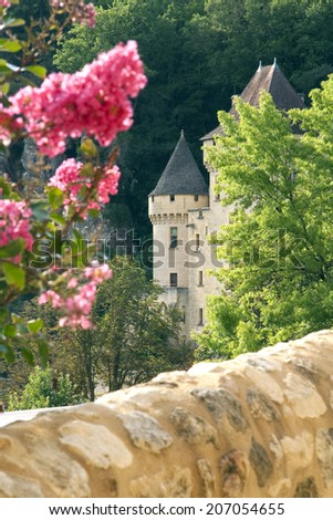 Turret in a French castle seen through trees and flowers with a stone wall in the foreground