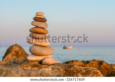 Turret pebbles at sunset with ocean on a blurry background. Relaxing stones. - stock photo
