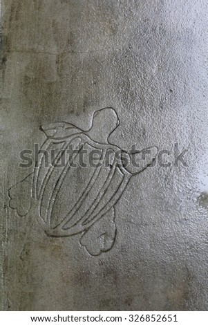 Turtle engraved on path. - stock photo