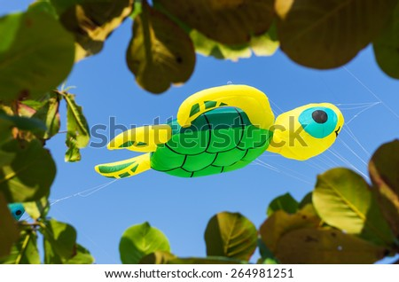 Turtle kite flying high in the clear blue sky, with leaf frame. - stock photo