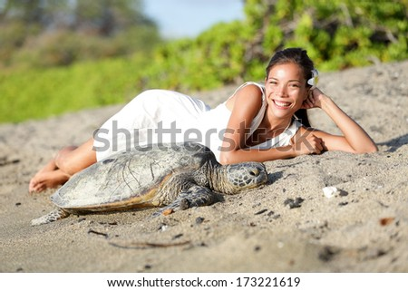 Turtle on beach - pretty asian caucasian mixed race woman wearing white dress lying beside. Sun shining in relaxed atmosphere. Nature scene with sea turtles, Big Island, Hawaii - stock photo