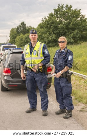 TURUNVAYLA, HELSINKI, FINLAND, JULY 9, 2014. A Finnish male and a female police couple standing in the side of the highway during a traffic raid in Turunvayla, Helsinki, Finland, on July 9th, 2014. - stock photo