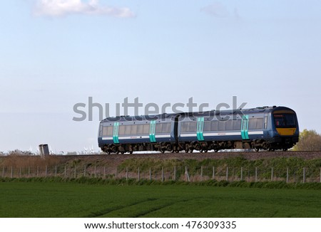 TURVES, UK - APRIL 22: An Abellio operated suburban commuter service runs along the fens en route to Ely on April 22, 2015 in Turves. Abellio call at 170 stations and operate 154 throughout the region