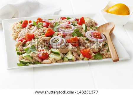 Tuscan bean and tuna salad with tomatoes, cucumber, parmesan and lemon vinaigrette, on a square white platter. - stock photo