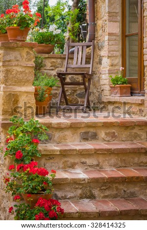 Tuscan brick house and chair in Monticchiello - stock photo