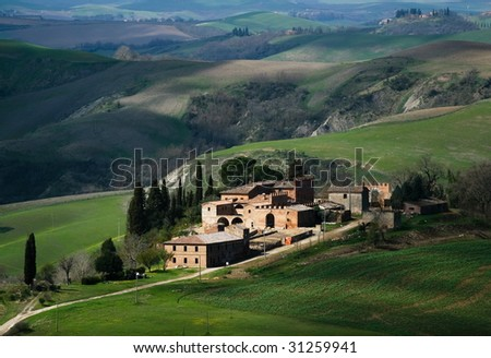 Tuscan farm in spring with green fields - stock photo