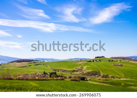 Tuscan landscape, view of the green Val D'Orcia Monticchiello and Pienza town in the background, in Italy - stock photo
