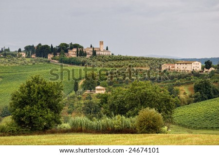 Tuscan landscape with hills and ancient village - stock photo