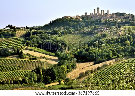 Tuscan landscape with vine yards and fields on hills crowned by the skyline of San Gimignano, Tuscany, Italy - stock photo