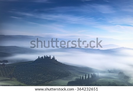 Tuscany blue foggy morning, farmland and cypress trees country landscape. Italy, Europe. - stock photo