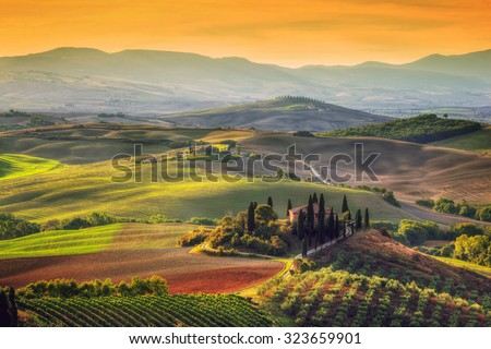 Tuscany landscape at sunrise. Typical for the region tuscan farm house, hills, vineyard. Italy - stock photo