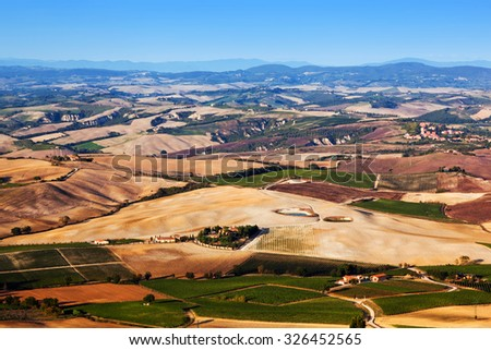Tuscany landscape panorama with blue sky. Typical for the region tuscan farm houses, hills, vineyards. Italy - stock photo