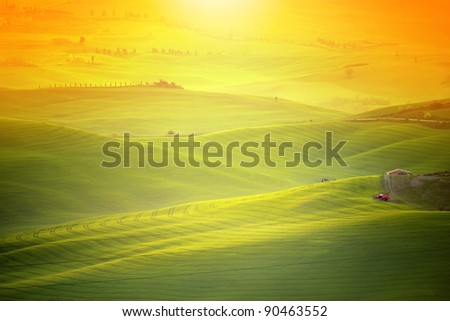 Tuscany landscape shot with orange gradual filter. Morning sunlight shines over the hilly landscape with thin haze. - stock photo