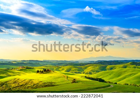 Tuscany, rural sunset landscape. Countryside farm, cypresses trees, green field, sun light and cloud. Volterra, Italy, Europe. - stock photo