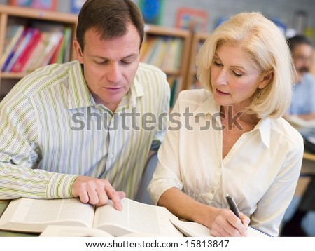 Tutor assisting mature student in library