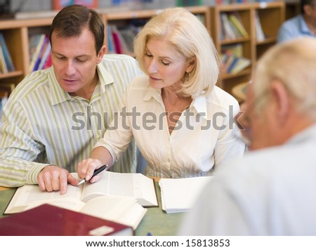 Tutor assisting mature student in library - stock photo