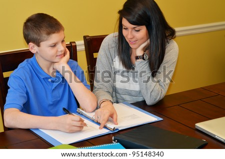 Tutor helping a young student with his studies - stock photo