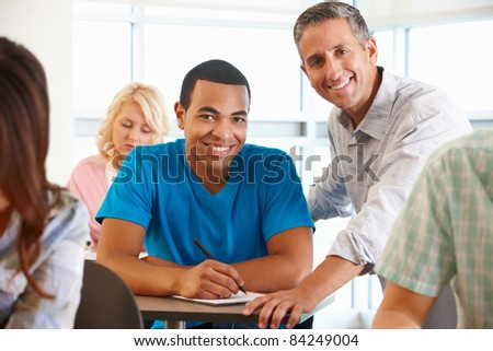 Tutor helping student in class - stock photo