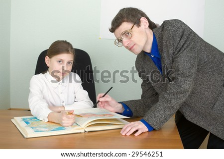 Tutor in a suit and schoolgirl with atlas