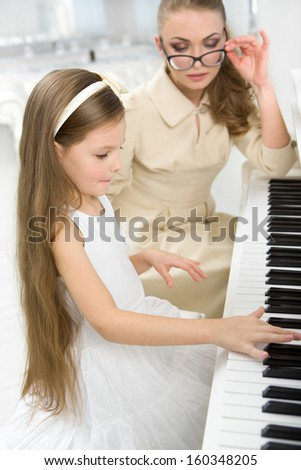 Tutor teaches little girl to play piano. Concept of music study and art - stock photo