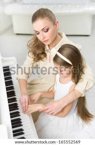 Tutor teaches little girl to play piano. Concept of music study and leisure - stock photo