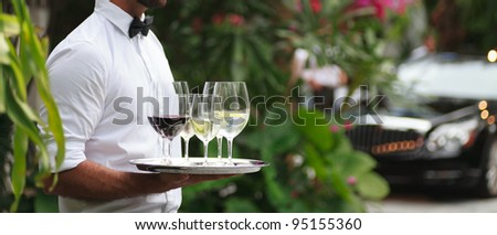 Tuxedo dressed waiter serving wine in a fancy outdoor setting. - stock photo