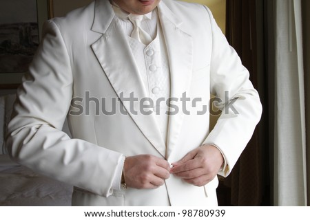 tuxedo / Standing groom in a white tuxedo. Image was taking during a wedding. - stock photo