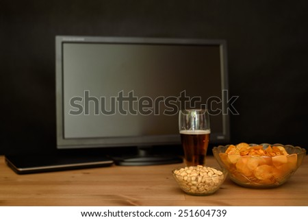TV and computer with unhealthy snack on table isolated on black background - stock photo - stock photo