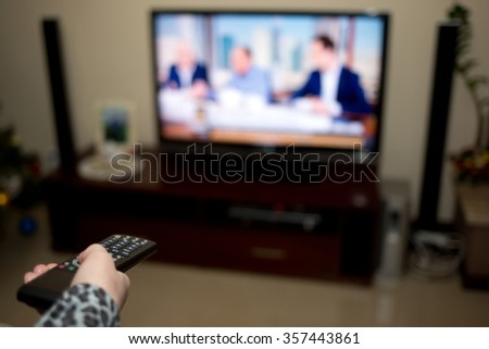 Tv and hand pressing remote control  - stock photo