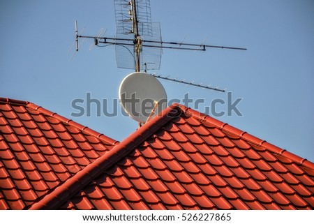 Tv Antennas And Satellite Dish For Television Mounted On The Tiled Roof Of House Isolated On