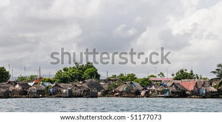 TV antennas on houses made of palm leaves - stock photo