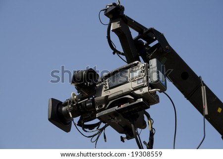 TV camera on the crane and with blue sky in the background - stock photo