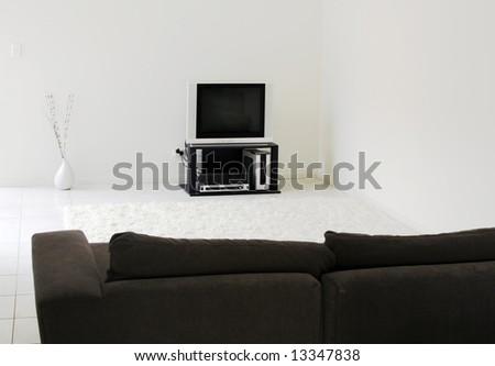 TV In Modern Living Room – White Tiles, Rug, Dark Sofa - stock photo