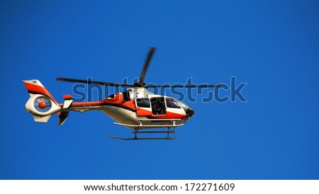 TV news helicopter with blur propeller at blue sky - stock photo