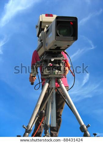 TV Professional studio digital video camera and cameraman over blue sky - stock photo