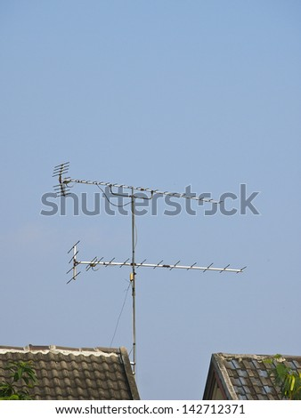 tv receiver antenna on roof house in sunny day - stock photo