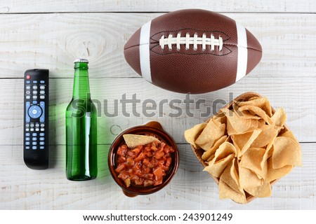 TV Remote, beer bottle, bowl of chips with salsa and an American style football on a rustic whitewashed wood surface. Horizontal format. Great for Super Bowl party themed projects. - stock photo