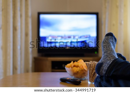 TV, television watching (refugee boat, news) with feet on the table and snacks - stock photo - stock photo