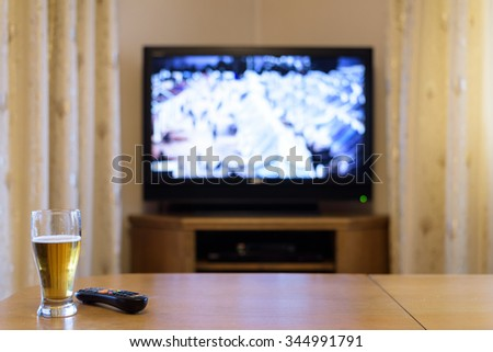 TV, television watching (refugee camp, news) with beer lying on the table - stock photo - stock photo