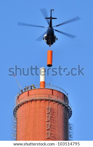 TV transmitter installation on the chimney with a helicopter Mi-8. Chimney power plant in Lodz, Poland 05/25/2012 - stock photo