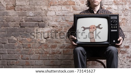 TV with a picture of a wrench in the hands of a seated man . - stock photo