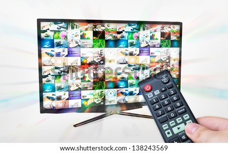 TV with multiple images gallery. Streaming glow effect. Hand hold remote control - stock photo