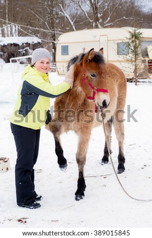 TVER, RUSSIA - FEBRUARY, 2016: Young girl touches horse at snow winter in russian village (country) near Tver, Russia, february, 2016
